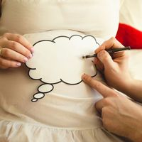 Hand Writing on Belly Dad Choosing Baby Name