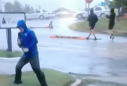 Hilarious fake news: Weather Channel reporter fakes hurricane-force winds while two guys casually stroll down the street behind him, wearing shorts